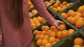 decidir : Girl in the supermarket chooses fruit, close-up. Female hand picks oranges in the supermarket.