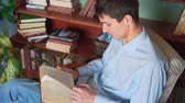 medio oriente : A young man reads a book while sitting in the home library, a man in a blue shirt and jeans holds a book and reads, having time on the background of bookshelves in the library. Side view.