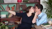 explicando : The guy and the girl are sitting in the home library, a man in a blue shirt and jeans, a girl in a dark dress. The girl and the guy pose, take a selfie, then kiss. Archivo de Video