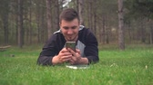 čtenář : A young guy is lying on the green grass in the forest and looks into the phone. Rest, relaxation, pleasure. Background - pine forest. Dostupné videozáznamy