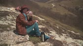 realizar : In the mountains sits a man in a cowboy hat, leather jacket, blue jeans and glasses. A man drinking tea from a thermos. Background of mountains and sky. Vídeos