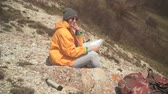 alpinista : A young girl with long dark hair in a yellow jacket and a gray cap sits in the mountains and looks at a tourist map. Background mountains, sky.