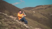 viaje : A young man in a yellow jacket, blue jeans sits in the mountains and enjoys the scenery, looking through a telescope, and then talking on the phone. In the background are hills and sky.