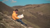 viaje : A young man in a yellow jacket, blue jeans and glasses sits in the mountains and see the traveler s map. Behind the background are mountains and sky. Archivo de Video