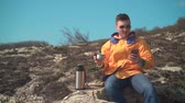 tramp : A young man in a yellow jacket, blue jeans and glasses sits in the mountains, enjoys the scenery and drinks tea from a thermos. In the background are hills and sky. Mountain landscape.