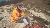 atlas : A young girl with long dark hair in a yellow jacket and a gray cap sits in the mountains and looks at a tourist map. Background mountains, sky.