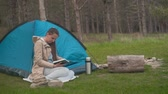 viaje : A young girl with long hair is sitting near a blue tent in the forest and reading a book. Background - pine forest. Archivo de Video