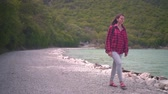 kombinéza : Medium shot of a young attractive girl in a red plaid shirt, posing for the camera. The girl goes along the shore of the lake on a warm day. Dostupné videozáznamy