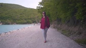 kombinéza : Medium shot of a young attractive girl in a red plaid shirt, posing for the camera. The girl goes dancing along the shore of the lake on a warm day.