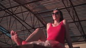analık : A beautiful pregnant girl in a red one-piece swimsuit and glasses sits on a sun lounger. Large metal canopy in the background.