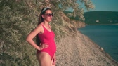 analık : Beautiful pregnant girl in a red one-piece swimsuit and glasses near a tree stands on the beach, smiling, enjoying the sunset. Stok Video