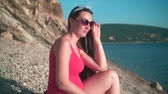 analık : Beautiful pregnant girl in a red one-piece swimsuit and glasses sits on the beach. Mountains in the background. Stok Video