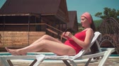 A beautiful pregnant girl in a red one-piece swimsuit is lying on a lounger by the pool against the background of a wooden house. The girl wears sunglasses.