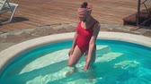 A beautiful pregnant girl in a red one-piece swimsuit and glasses stands knee-deep in the pool water.
