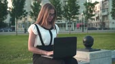 Caucasian young business woman in white shirt and glasses sits on a bench in the street and works behind a laptop. Close-up, the girl puts the glasses on her eyes and continues to work.