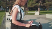 Caucasian young business woman in white shirt and glasses sits on a bench on the street and works. The girl writes in a notebook, looking at the laptop. The camera shoots from the side. Videos