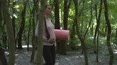 yogamatte : Pregnant woman doing yoga in the park. A girl is walking in the park with a rug in her hand, holding her other hand on her tummy. Stock Footage