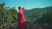 vinařství : A pregnant girl in a red dress is standing in a vineyard. A pregnant girl with long hair in glasses is standing in a vineyard and holding hands behind her head.