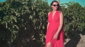 bağcılık : A pregnant girl in a red dress is walking through the vineyard. A pregnant girl with long hair in glasses walks through the vineyard. The average plan.