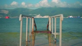cena de tranquilidade : Descent to the sea. Metal construction on a concrete base. In the background there is a sea of turquoise color and mountains, beautiful clouds over the mountains. The concept of the holiday season.