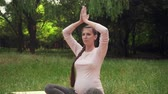 yogamatte : A pregnant woman practices yoga in the park while sitting on a rug, sitting in a lotus position, holding her arms above and meditating. Relaxing and being in a light lotus.