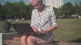 publicidad : Caucasian young business woman in a white shirt with black peas sitting on a bench on the street and working behind a laptop. Overall plan.