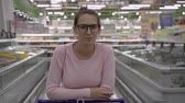 mide : A young pregnant woman with glasses in a supermarket stands leaning on a trolley. Woman doing grocery shopping at the supermarket. Stok Video