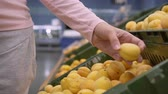 seçen : Girl in the supermarket chooses fruit, close-up. Female hand picks fruits in the supermarket.