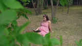 fertilidade : A pregnant girl sitting on the grass in the park. A happy girl with long dark hair in a striped white-red dress is reading a book. In the background, trees, people passing by. Vídeos