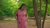 fertilidade : A pregnant girl walks through the park. A girl with long dark hair in a striped white and red dress goes smiling and dancing among the trees.