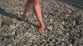 suntan : Close-up. Female sexy tanned legs walk barefoot on the rocky seashore.