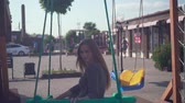 amusing : Cute young girl walks in an urban environment. Happy girl in a gray dress swinging on a swing at the playground. Stock Footage