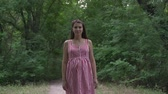 pohlazení : Pregnant girl in the park on a background of green trees. A girl with long dark hair in a striped white-red dress walks through the park. Dostupné videozáznamy
