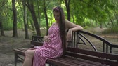 fertilidade : Pregnant girl in the park on a background of green trees. A girl with long dark hair in a striped white-red dress sits on a bench in the park and strokes her tummy.