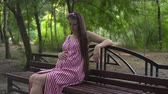 pohlazení : Pregnant girl in the park on a background of green trees. A girl with long dark hair in a striped white-red dress sits on a bench in the park and strokes her tummy.