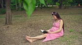 ábrándozás : A pregnant girl sitting on the grass in the park. A happy girl with long dark hair in a striped white-red dress is reading a book. In the background, trees, people passing by. Stock mozgókép