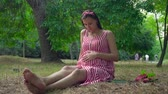 doğurganlık : A pregnant girl sitting on the grass in the park. Happy girl with long dark hair in a striped white-red dress strokes her tummy. In the background, trees, people passing by.