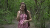 fertilidade : A pregnant girl walks through the park. A girl with long dark hair in a striped white-red dress speaks by telephone and strokes her tummy.