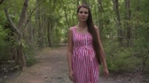 fertilidade : Pregnant girl in the park on a background of green trees. A girl with long dark hair in a striped white-red dress walks through the park. Vídeos