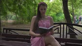 fertilidade : A pregnant girl is sitting on a bench in the park. A girl with long dark hair in a striped white-red dress enthusiastically reads a book on a bench.