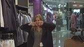 giymek : Cute young girl chooses clothes. Happy girl in a gray dress in the mall looks at clothes on hangers, trying on things. Stok Video