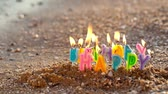 decor : Colourful birthday candles spelling out the alphabet letters - Happy Birthday - standing upright in beach sand burning on a seashore at the edge of the sea