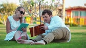 人 : Young couple spending free time on the green lawn.  Woman using a touchpad, man reading a book 影像素材