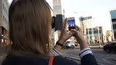 tallin : Close-up shot of a woman taking pictures of modern city buildings using her smartphone Stock Footage