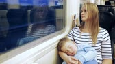 evening : Young woman looking out the train window in the evening, little son sleeping on her lap