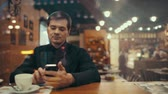 Young businessman drinking coffee and typing sms in a cafe. View through the glass with weak city reflection Stock Footage