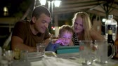 play : Family of three in outdoor cafe in the evening. Boy playing on touch pad, happy parents watching Stock Footage