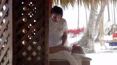 terapist : Female massage therapist finishing spa treatment and covering the womans back with sheet. Tropical beauty spa