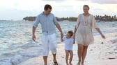 wrack : Happy family walking along the shore in tropics. They holding hands, water washing their feet