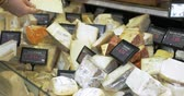 different cheeses : Woman looking over different types of cheeses in the shop. Variety of choice in kinds and prices
